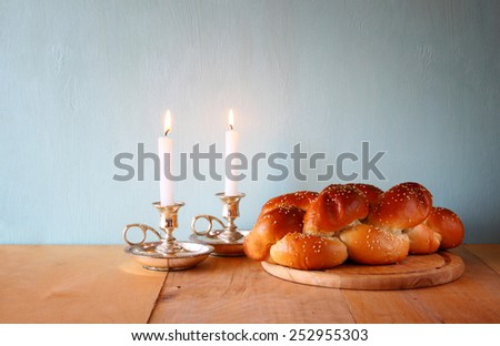 shabbat image. challah bread, wine and candelas on wooden table. - stock photo