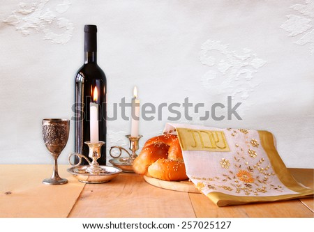 shabbat image. challah bread,wine and candelas on wooden table.  - stock photo