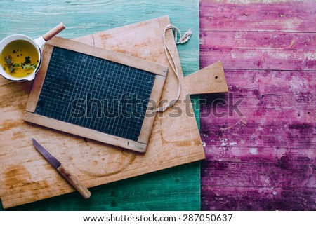 Shabby chic kitchen cookery background with a wood chopping board, seasoned oil and a vintage school slate with copyspace over a colorful wooden rustic table - stock photo
