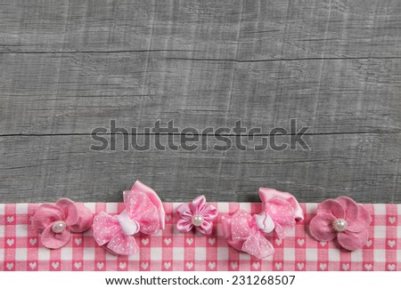 Shabby chic wooden grey background with pink ribbon on white checked frame for decoration. - stock photo