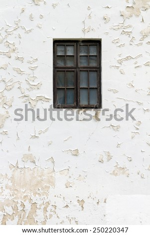 Shabby white wall of an abandoned house with a closed glass window - stock photo