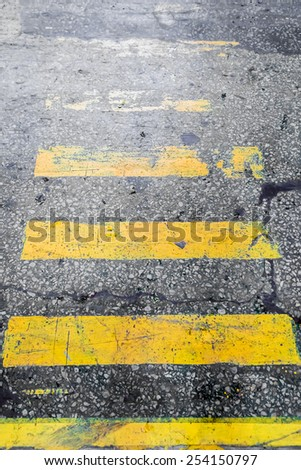 Shabby yellow stripes crosswalk on the old concrete surface - stock photo