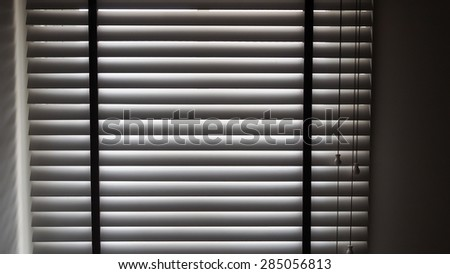 Shadow from wooden Venetian blind with drawstring. - stock photo