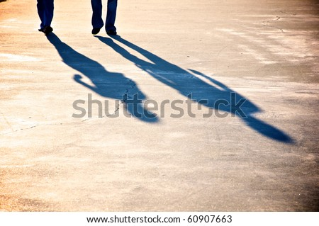 Shadow of a couple walking - stock photo