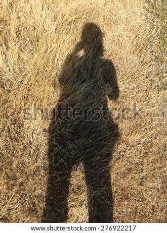 Shadow of a person taking a picture on the ground. - stock photo