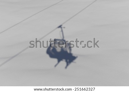 shadow of a skier on a skilift in the alps - stock photo