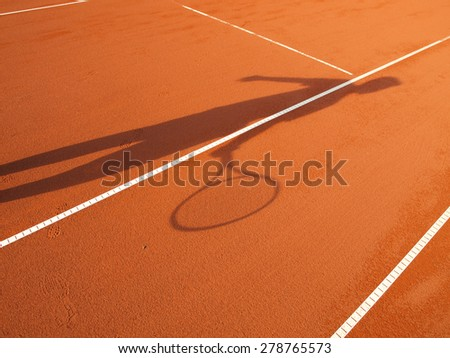 shadow of a tennis player in action on a tennis court (conceptual image) - stock photo