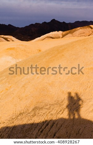 Shadow of active couple hiking in colorful shale mudstone badlands of Death Valley National Park, California, USA - stock photo