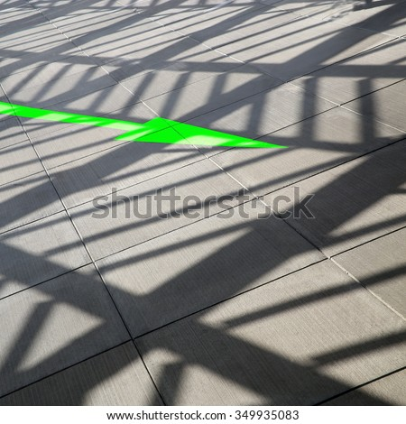 Shadow of contemporary architecture. Pavement tiles under transparent glazed aluminum structure in sunny day. Office building or shopping mall premises with green arrow showing direction of traffic. - stock photo