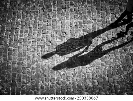 Shadow of couple holding hands in black and white with vignette - stock photo