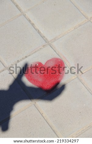 shadow of hand with red heart - stock photo