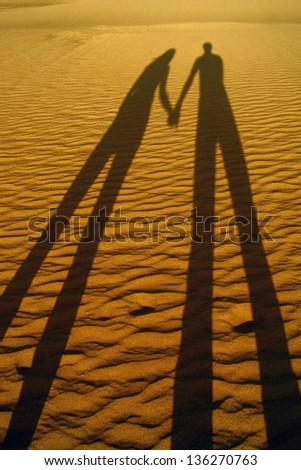 Shadow of  loving couple on the beach sand - stock photo