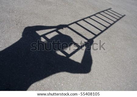 Shadow of man climbing ladder on asphalt - stock photo