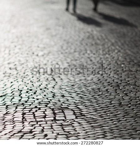 shadow of pedestrians on cobblestone street  - stock photo