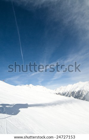 Shadow of snow gun at ski slope - stock photo