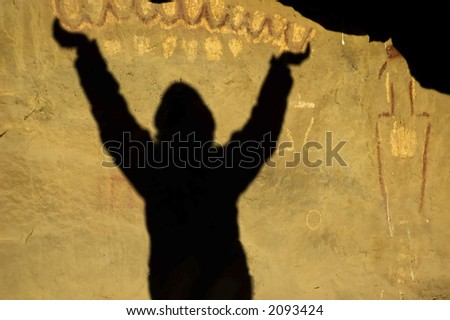 shadow of woman holding pictograph design at ancient native american rock art site - stock photo