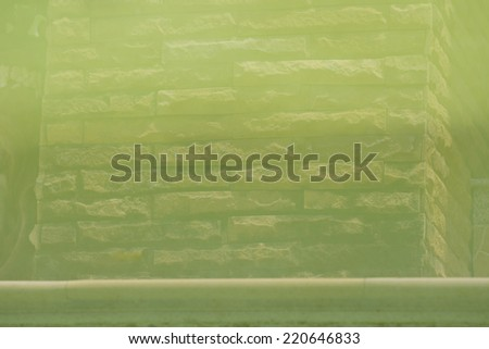 shadow rock texture on green water  - stock photo