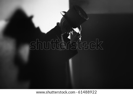 Shadowgraph of the man in black coat and hat standing near the wall and his shadow. Monochrome photo with natural darkness. Artistic grain added for movie effect - stock photo