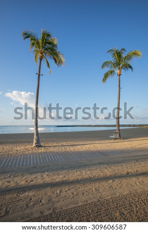Shadows and sunlight from a morning view of Waikiki Beach in colors of tan, green,yellow,blue, and white. - stock photo