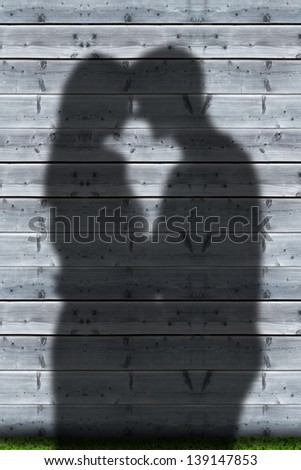 Shadows of couple embracing on wooden boards wall - stock photo