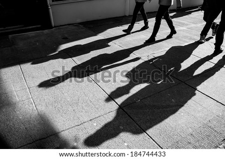 Shadows of four walking pedestrians projected on the sidewalk - stock photo