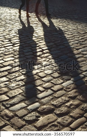Shadows of people walking on the cobblestone street - stock photo