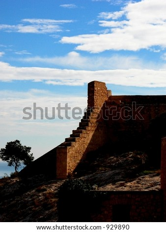 Shadows on an ancient castle wall overlooking the sea in spain - stock photo