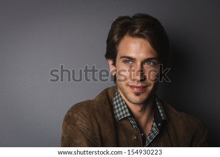 Shadowy portrait of a handsome young man with a charismatic smile on a dark grey background with copy space - stock photo