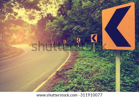 Shady beautiful curved road with cool, sunshine and the sign of hope on vintage style. Focus on the sign. - stock photo