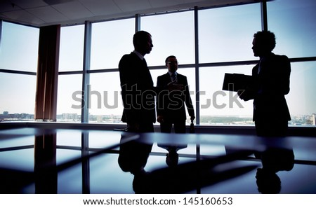 Shady image of a manager discussing business matters with her subordinates - stock photo
