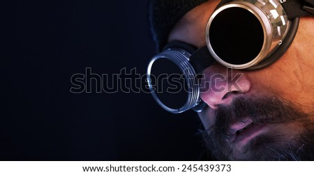 Shag beard and mustache man with goggles overlooking copy space - stock photo