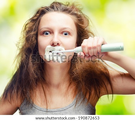 Shaggy young woman using electric toothbrush. - stock photo