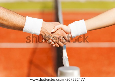Shaking hands after good game. Close-up of man and woman in wristband shaking hands upon the tennis net  - stock photo