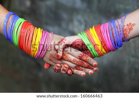 Shaking hands decorated with colorful bracelets and henna tattoo - stock photo