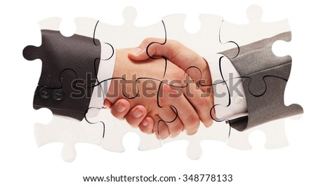 shaking hands inside puzzle pieces - stock photo