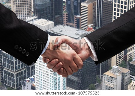shaking hands on background of city - stock photo