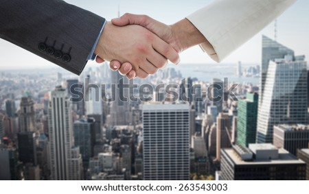 Shaking hands over eye glasses and diary after business meeting against new york - stock photo