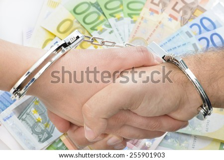 Shaking hands with handcuffs with money in background - stock photo