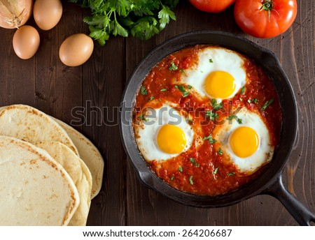 Shakshuka with eggs, tomato, and parsley in a cast iron pan. - stock photo