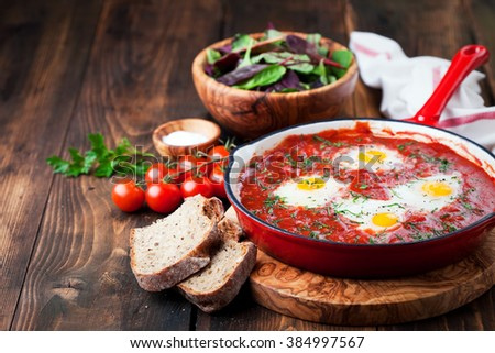 Shakshuka with tomatoes and eggs in a cast iron pan, selective focus - stock photo