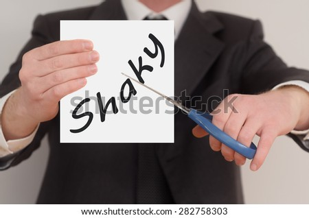 Shaky, man in suit cutting text on paper with scissors - stock photo