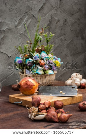 Shallots , Onion , Garlic , Chopping board , Knife , flower with basket on the table - stock photo