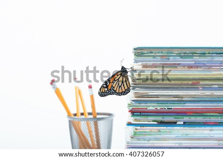 Shallow depth of field catches one monarch butterfly climbing up a pile of children's story books. A finishing touch with pencils faded out in the white background. Horizontal with copy space. - stock photo
