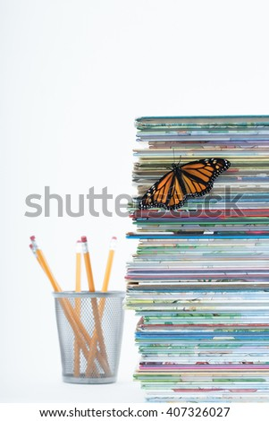 Shallow depth of field catches one monarch butterfly with open wings climbing up a pile of children's books. A finishing touch with pencils faded out in the white background. Vertical with copy space. - stock photo