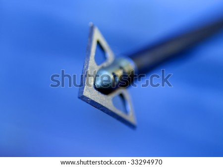 Shallow depth of field image of an arrow flying in the direction of the viewer. - stock photo