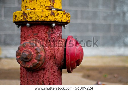 Shallow depth of field image of an old fire hydrant with cracking and peeling paint. - stock photo