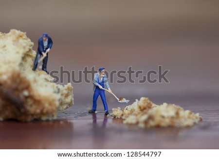 shallow depth of field image of miniature figures at work - stock photo