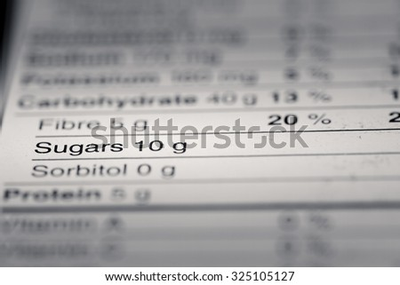 Shallow depth of Field image of Nutrition Facts Sugar Information we can find on a grocery Store Product. - stock photo
