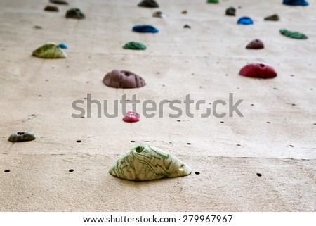 shallow depth of field looking up a climbing wall focused on the foot grip closest to the camera - stock photo