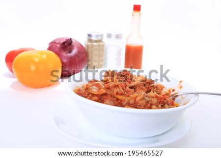 Shallow depth of field on Big bowl of chicken jambalaya with Creole Seasoning on white background with vegetables and spices and bright back lighting.  Horizontal format with copy space - stock photo